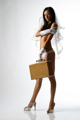 Attractive charming girl in lingerie stands with a suitcase
