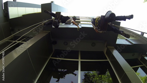 Window Cleaners Outside of a Building Hanging From a