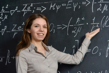 Portrait of a pretty student doing maths on a blackboard
