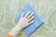 female hand cleaning kitchen tiles with sponge
