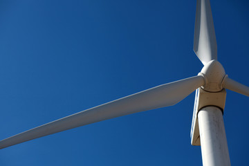 Wind mill, a turbine close against blue sky