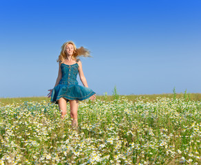 The beautiful happy young woman in the field of chamomiles..