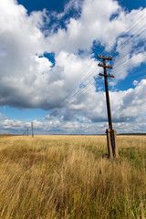 Old wooden electric pillar in the field..