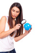 Pretty female holding a globe and using a magnifying glass while