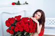 Beautiful brunette woman with red roses flowers bouquet in moder