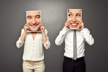 woman and man holding smiley faces