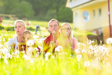 family sitting in meadow in front of home