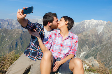 Couple Taking Self Portrait at Top of Mountain