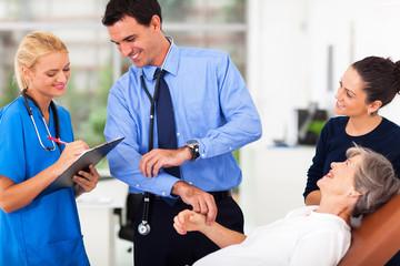 doctor and nurse recording senior patient's pulse
