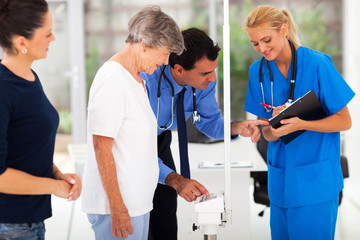 medical doctor monitoring senior patient's weight