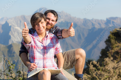 Young Couple with Thumbs Up at Top of Mountain