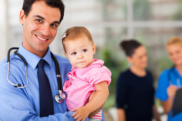 pediatrician holding baby patient