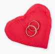 Big red heart from the fabric, two gold wedding rings on the