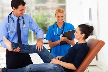 orthopaedist examining female patient's leg