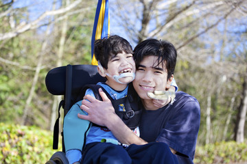 Little disabled boy in wheelchair hugging older brother outdoors