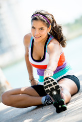Athletic woman stretching outdoors