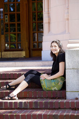 Young teen girl enjoying sunshine, sitting on brick steps outdoo