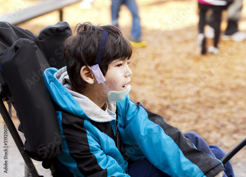 Disabled boy in wheelchair on playground. Has cerebral palsy.