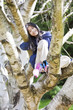 Young girl sitting in birch tree, smiling
