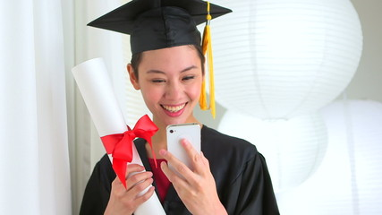Mixed Race Asian graduate taking picture with smart phone