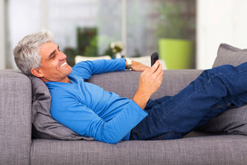 middle aged man reading text message on mobile phone