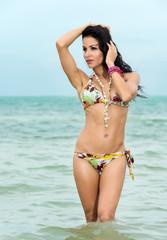 Sexy woman in a bikini knee deep in the sea