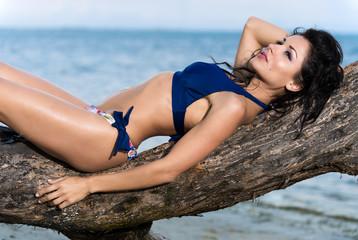 Woman in a bikini relaxing on a branch