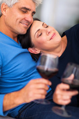 mature couple enjoying wine at home