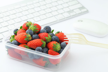 Health lunch with strawberry and blueberry mix in office