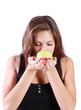 Beautiful brunette girl with closed eyes sniffs green apple