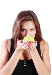 Beautiful brunette girl sniffs green apple isolated on white