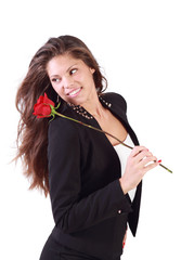 Smiling woman with flying hair holds rose on her shoulder