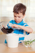 boy puts plant in pot