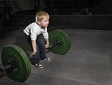 Determined Young Boy trying to lift Heavy weights poster