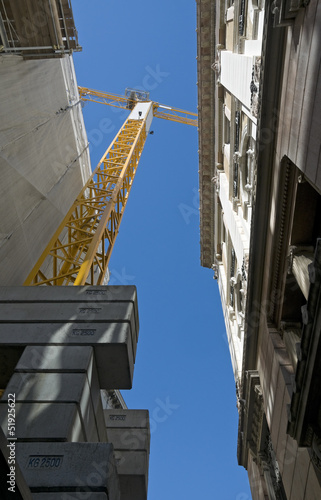 Narrow alley surrounded by old palaces with building site crane