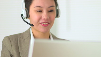 Asian customer service representative with headset in call cente