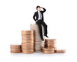 business man sitting on Stacks of money coin
