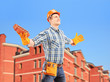 Happy worker holding a brick and spreading arms with a building
