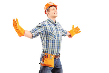 Happy manual worker with helmet spreading arms