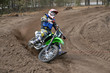MX racer on a motorcycle in the reversal sandy track