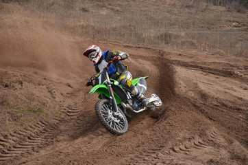 MX motorcycle with rider shoots out of a turn
