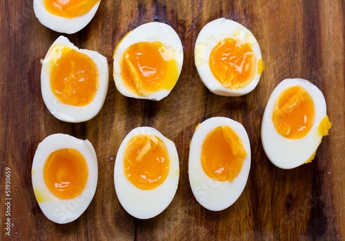 Hard boiled eggs, sliced in halves on wooden background