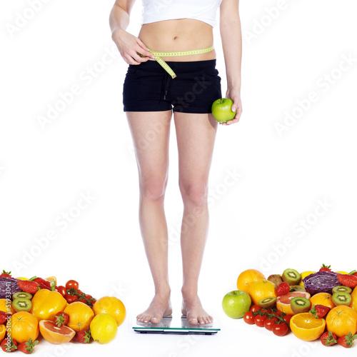 Gemüse und Obst hält schlank und fit, Frau auf Waage