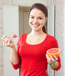girl in red eats grapefruit
