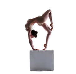 Flexible young woman posing on cube