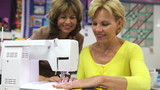 Teacher Showing Woman How To Sew Using Electric Machine