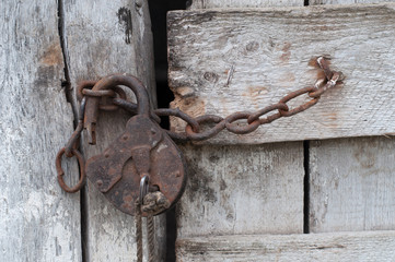 Lock with a chain on an old wooden door