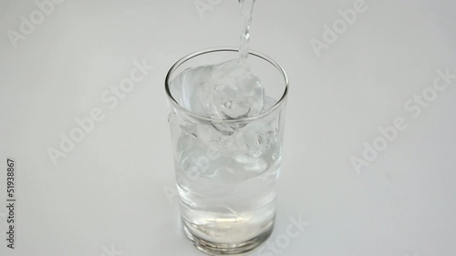 Pouring drinking water into a glass in white background