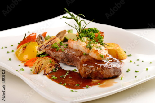 Delicious juicy barbequed steak and prawns with grilled tomato