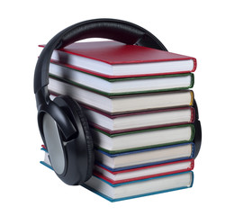 Headphones worn on a stack of books with color covers.